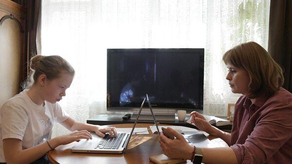 Мама и дочь перед мониторами ноутбуков