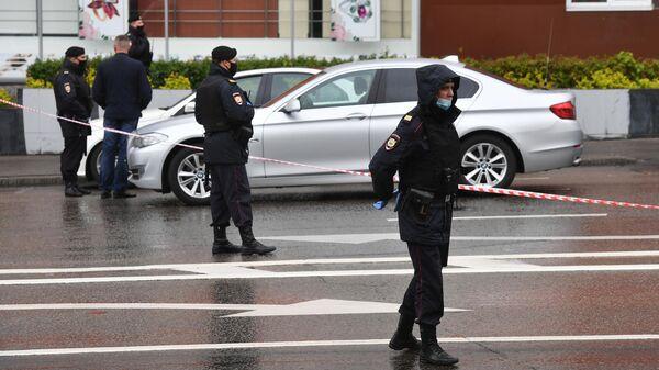 Сотрудники полиции в оцеплении у отделения Альфа-банка в центре Москвы, откуда поступило сообщение, что неизвестный удерживает несколько человек и угрожает взорвать отделение