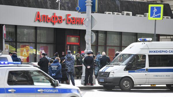Сотрудники полиции у отделения Альфа-банка в центре Москвы, откуда поступило сообщение, что неизвестный удерживает несколько человек и угрожает взорвать отделение