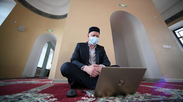 Верующий смотрит прямую трансляцию праздничного вагаза в Галеевской мечети в Казани