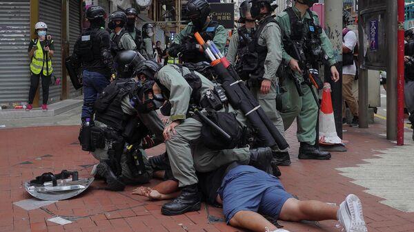Сотрудники полиции во время задержания участника акции протеста в Гонконге