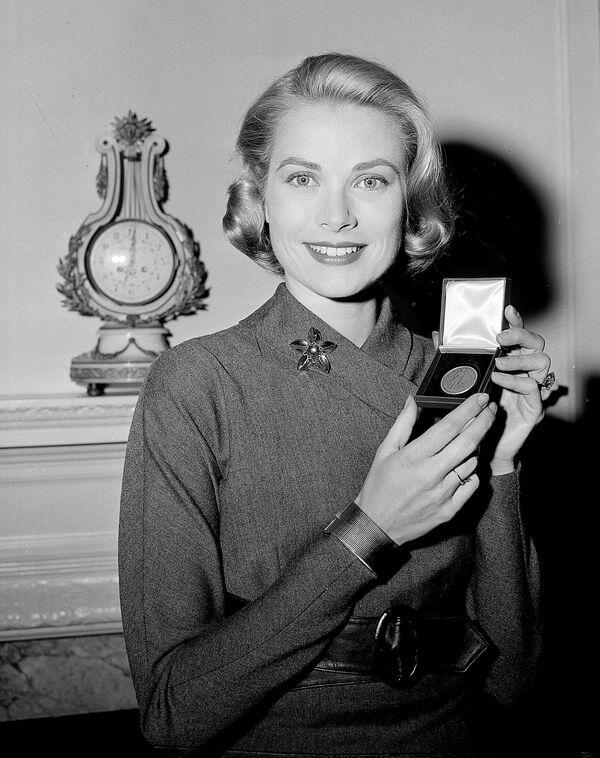 Актриса Грейс Келли с серебряной медалью, врученную ей Министерством финансов США. 30 марта 1956 года