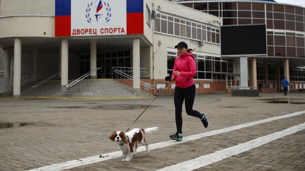 Девушка во время пробежки на улице Береговой в Краснодаре