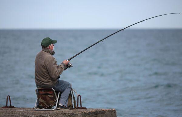 Рыбак на набережной Алушты после отмены режима самоизоляции в Крыму