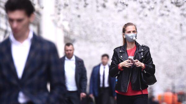 Девушка в защитной маске на Никольской улице в Москве