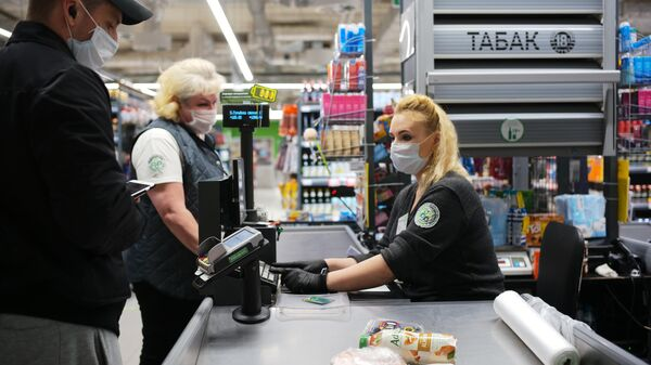 Покупатель оплачивает покупки на кассе в супермаркете Перекресток
