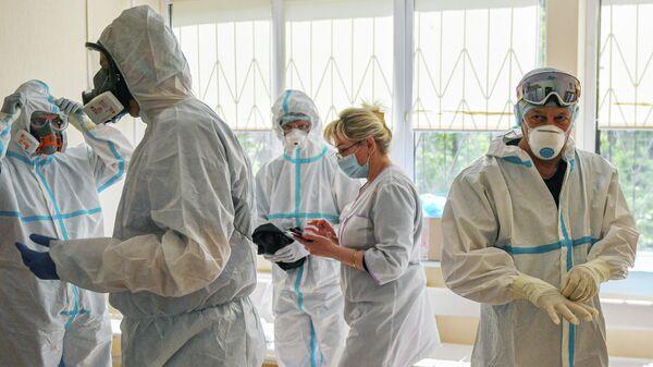 Врачи надевают костюмы в зеленой зоне перед началом работы с зараженными COVID-19