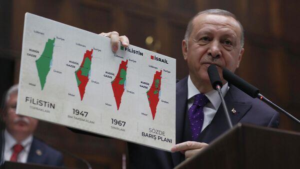 Президент Турции Реджеп Тайип Эрдоган держит плакат, на котором изображены территории Палестины