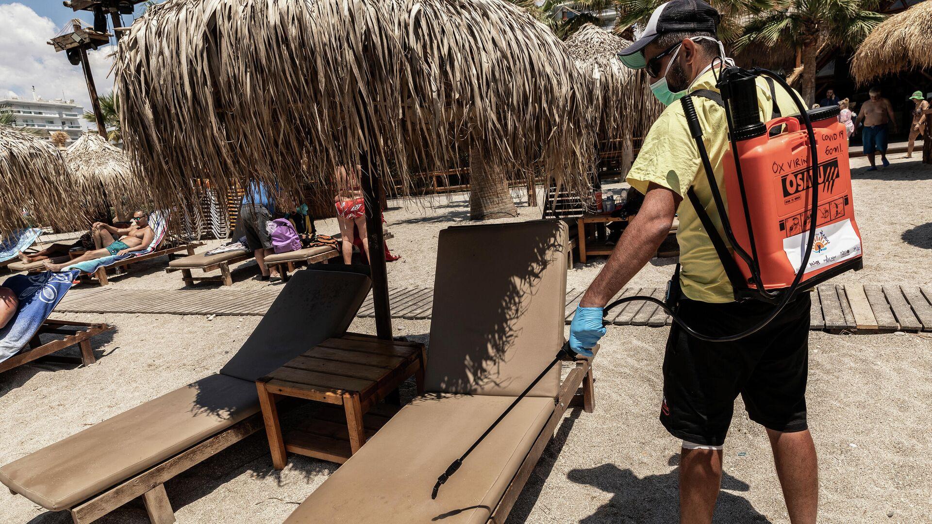 Рабочий дезинфицирует лежаки на городском пляже Алимос в пригороде Афин - РИА Новости, 1920, 23.06.2021