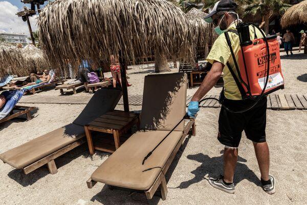 Рабочий дезинфицирует лежаки на городском пляже Алимос в пригороде Афин