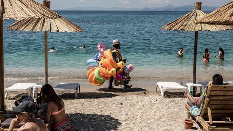 Отдыхающие и продавец игрушек на городском пляже Алимос в пригороде Афин