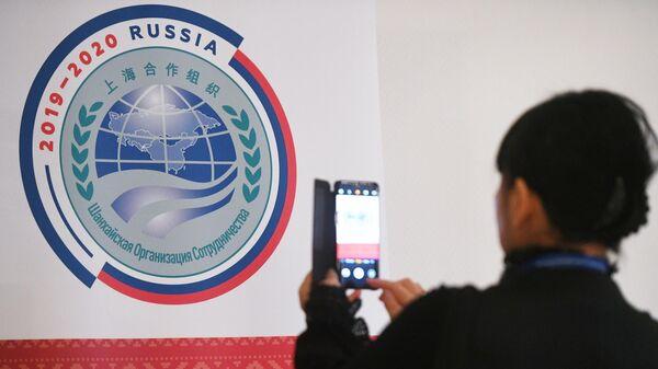 Участница совещания руководителей министерств и ведомств науки и техники государств-членов ШОС фотографирует логотип председательства России в ШОС