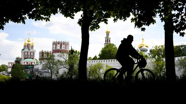 Мужчина катается на велосипеде в сквере у Новодевичьего женского монастыря в Москве