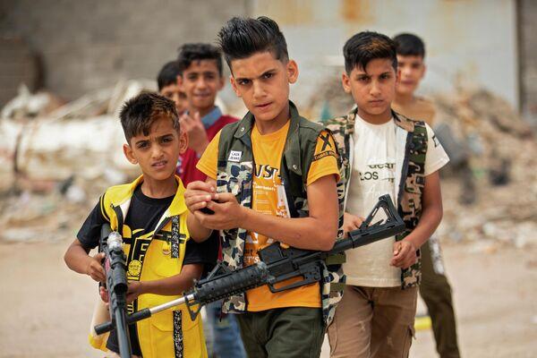 Дети играют с пластиковыми ружьями в Басре, Ирак