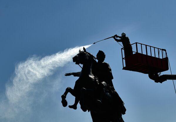 Сотрудник коммунальной службы моет памятник Петру I на Сенатской площади в Санкт-Петербурге