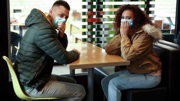 Молодые люди в защитных медицинских масках за столиком в кафе