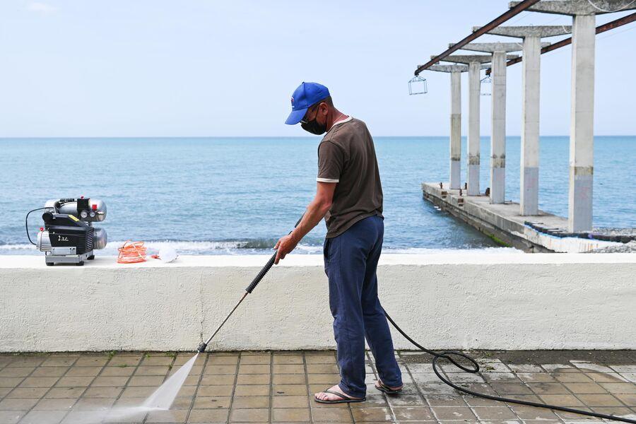 Мужчина моет набережную пляжа Чайка-1 в Сочи