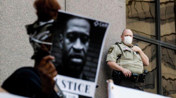 Участники акции протеста с портретом Джорджа Флойда у здания муниципалитета в Миннеаполисе