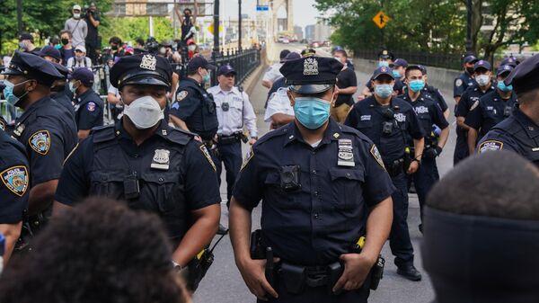 Полицейские стоят в оцеплении во время протеста, вызванного смертью афроамериканца Джорджа Флойда, на одной из улиц Нью-Йорка
