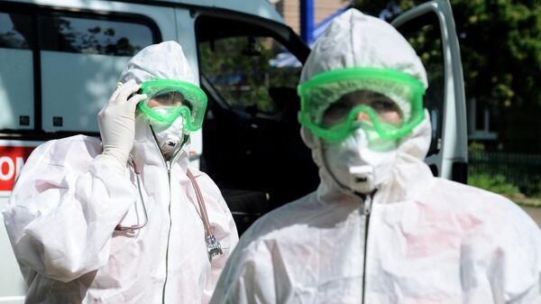 Фельдшеры в противоэпидемических костюмах во время выезда к пациенту