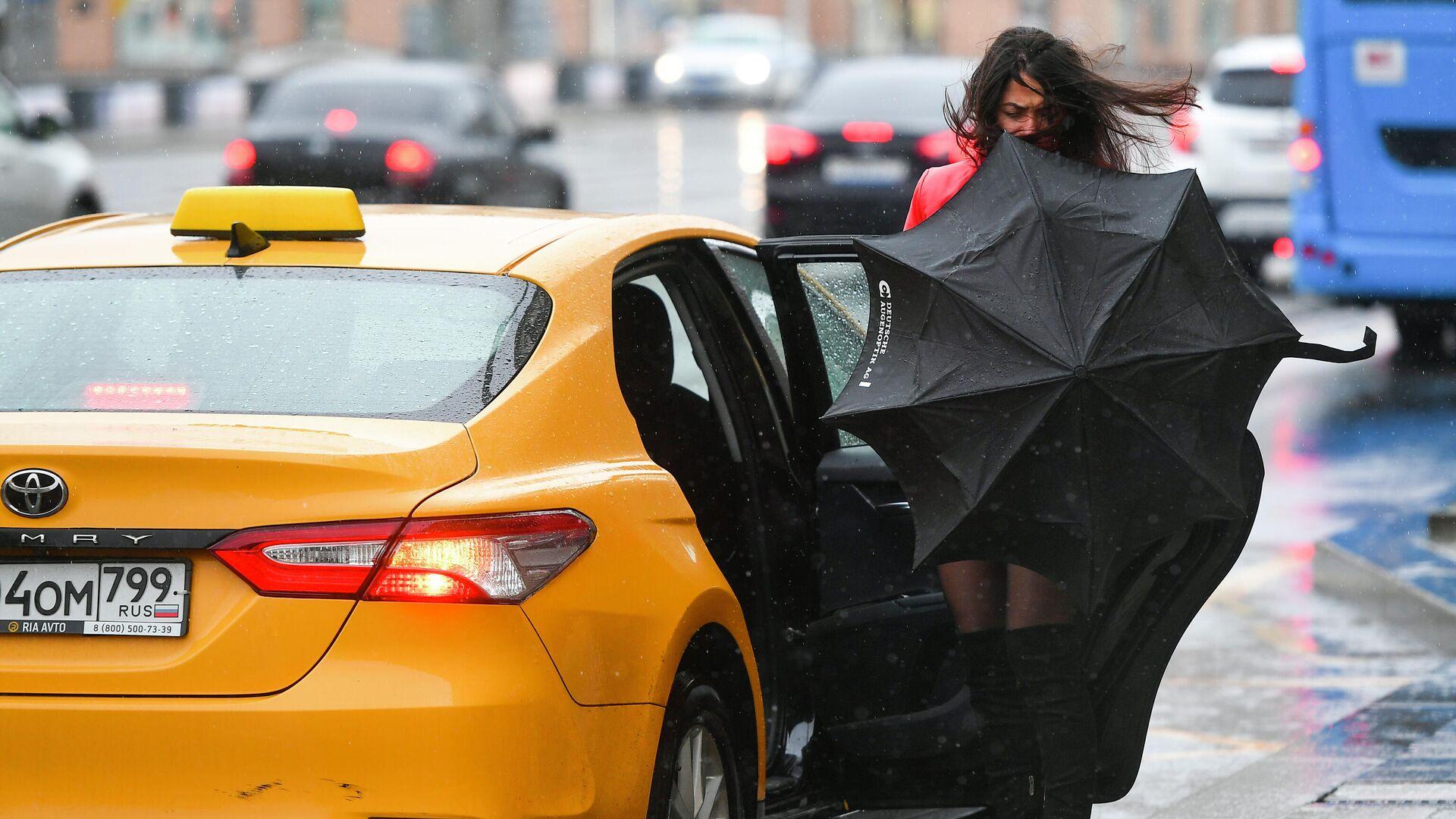 Девушка садится в такси во время дождя в Москве - РИА Новости, 1920, 21.06.2021