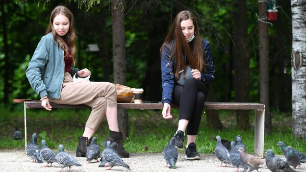 Девушки кормят голубей в парке имени Горького в Казани