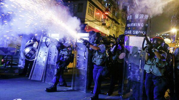 Сотрудники полиции во время пускают слезоточивый газ во время протестов в Гонконге