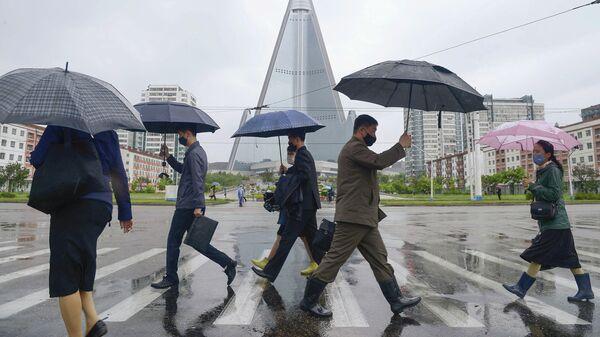 Прохожие в медицинских масках на улице Пхеньяна, КНДР
