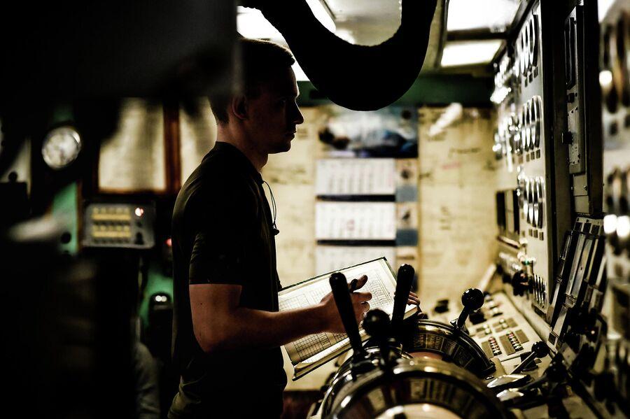 Моторист снимает параметры двигателей в машинном отделении судна Адмирал Владимирский