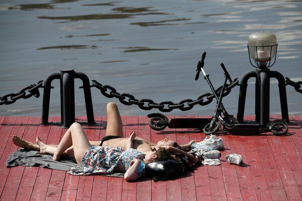 Люди загорают в Центральном парке культуры и отдыха имени Горького в Москве
