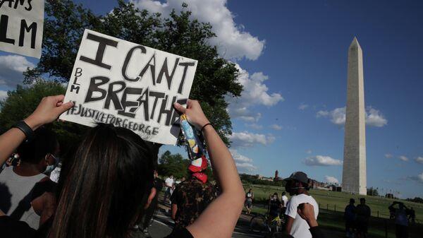 Протестующий с плакатом Я не могу дышать во время митинга возле памятника Вашингтону в США