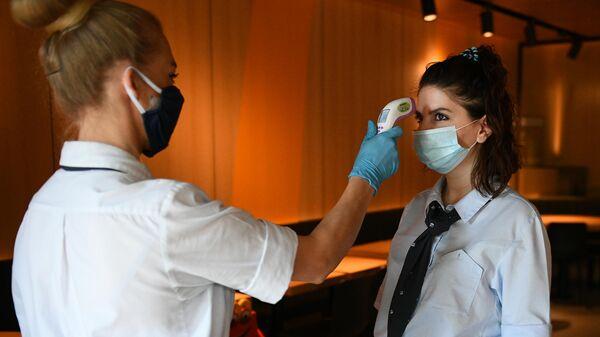 Менеджер ресторана Макдоналдс измеряет температуру коллеге