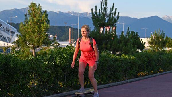Девушка катается на скейте по набережной пляжа ПТГ Сириус в городе Сочи