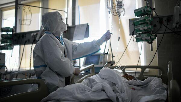 Врач проверяет капельницу у пациента