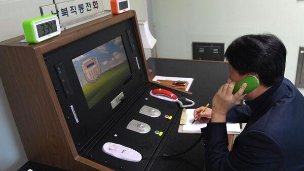 Южнокорейский чиновник проверяет прямую телефонную линию связи с КНДР в приграничной деревне Панмунджом