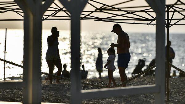 Люди отдыхают на пляже в поселке Новофедоровка Сакского района