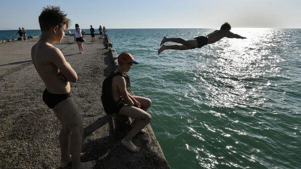 Юноша прыгает с пирса в море на набережной в поселке Новофедоровка Сакского района