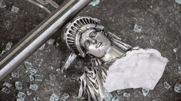 Разбитая фигура Статуи Свободы возле разграбленного сувенирного магазина в Нью-Йорке