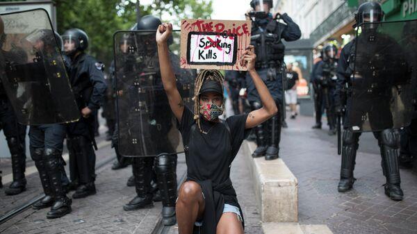 Протестующий на коленях перед французской полицией с табличкой Полиция убивает в Марселе, Южная Франция