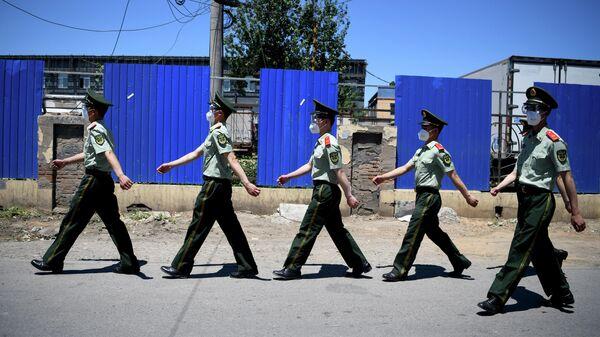 Китайские полицейские проходят мимо закрытого рынка Синьфади в Пекине