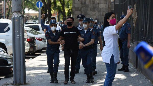 Сотрудники правоохранительных органов Армении задерживают участника акции у здания парламента в Ереване. 16 июня 2020