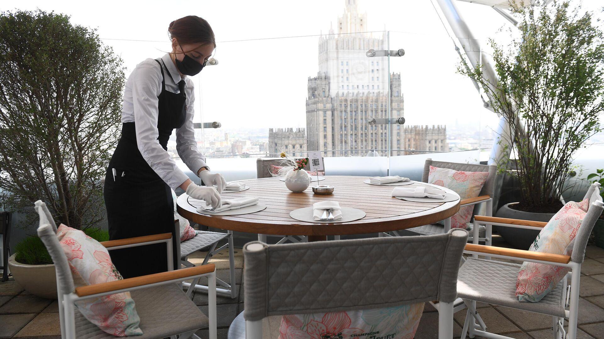 Официантка в защитной маске на открывшейся летней веранде ресторана Сахалин в Москве - РИА Новости, 1920, 30.03.2021