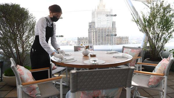 Официантка в защитной маске на открывшейся летней веранде ресторана Сахалин в Москве