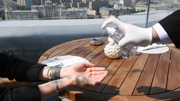 Дезинфекция рук посетительницы на открывшейся летней веранде ресторана Сахалин в Москве