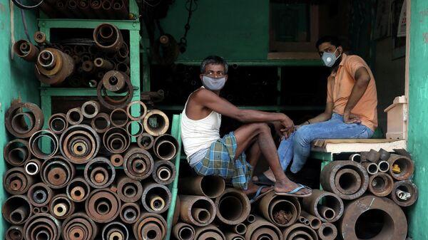 Работники магазина по продаже металлических труб на оптовом рынке в Калькутте
