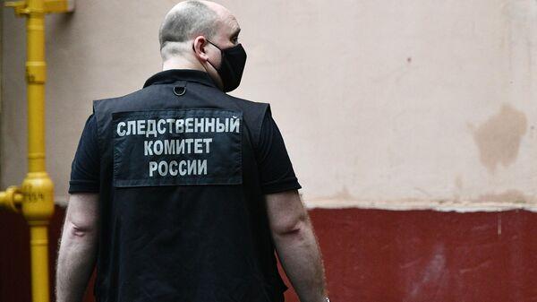 Сотрудник следственного комитета у жилого дома на севере Москвы, где мужчина открыл стрельбу