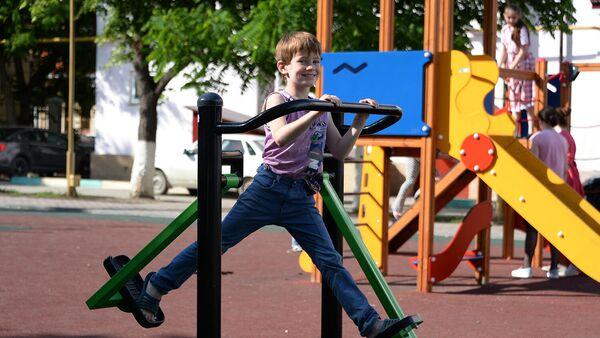 Мальчик занимается на уличном тренажере