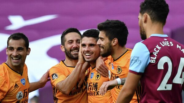 Wolverhampton Wanderers' Portuguese midfielder Pedro Neto (C) celebrates scoring their second goal during the English Premier League football match between West Ham United and Wolverhampton Wanderers at The London Stadium, in east London on June 20, 2020. (Photo by Ben STANSALL / POOL / AFP) / RESTRICTED TO EDITORIAL USE. No use with unauthorized audio, video, data, fixture lists, club/league logos or 'live' services. Online in-match use limited to 120 images. An additional 40 images may be used in extra time. No video emulation. Social media in-match use limited to 120 images. An additional 40 images may be used in extra time. No use in betting publications, games or single club/league/player publications. /