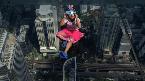 Девочка наблюдает солнечное затмение в Бангкоке, Таиланд