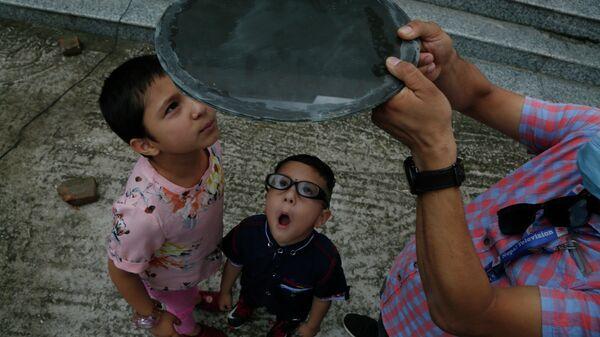 Дети наблюдают солнечное затмение в Катманду, Непал